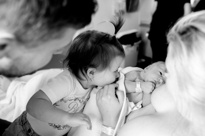 big sister kissing newborn sibling in hospital
